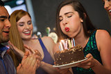 Attractive woman blowing the candles on her birthday cake