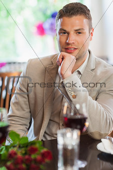 Smiling handsome man waiting for his girlfriend at restaurant