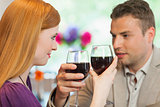 Handsome man having glass of wine with his pretty girlfriend