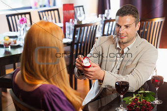 Handsome man proposing marriage to his pretty girlfriend