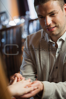 Handsome man putting on ring on his fiances finger