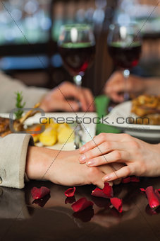 Close up on couple holding hands during dinner