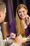 Gorgeous woman smiling at her husband during dinner
