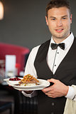 Handsome waiter serving appetizing duck dish