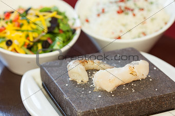Prawn and white fish on hot stone for cooking