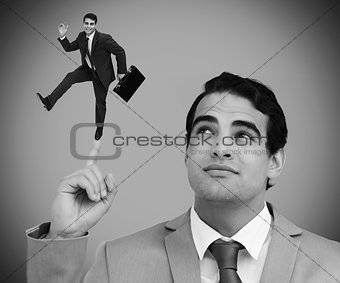Thoughtful businessman showing shrunk colleague dancing on his finger