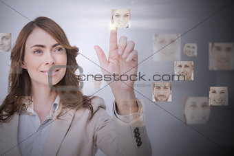 Smiling businesswoman selecting digital interface