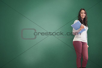 Smiling brunette holding notebook posing
