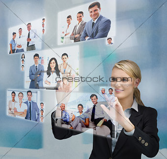 Blonde businesswoman selecting image from digital interface