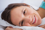Pretty woman lying in bed looking into the camera