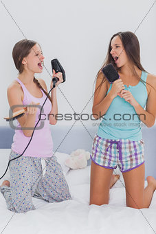 Two girls on bed singing into their hairbrushes