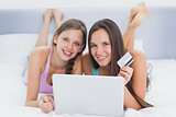 Friends shopping online on bed using laptop