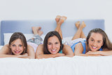 Three girls on bed looking at camera