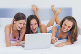 Friends lying on bed with laptop