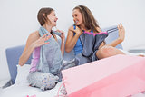 Teen girls sitting on bed after shopping
