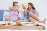 Friends enjoying breakfast in bed