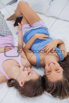 Two girls lying on bed and using phone
