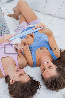 Girls lying in bed with tablet
