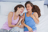 Girls wearing pajamas lying in bed and laughing