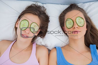 Friends lying in bed with cucumber slices on eyes