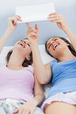 Girls lying in bed holding tablet