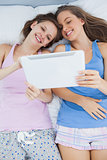 Smiling girls lying in bed holding tablet