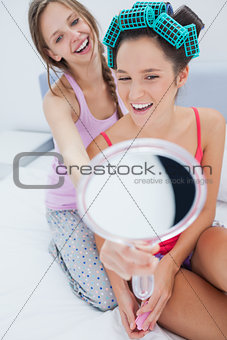 Girl wearing rollers looking in mirror and talking to friend