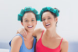 Girls in hair rollers and pajamas smiling at camera