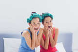 Friends with hair rollers on sitting in bed