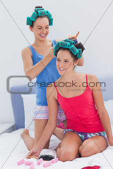 Girls in hair rollers and pajamas chatting