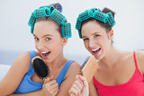 Friends in hair rollers singing into their hairbrushes