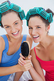 Happy girls in hair rollers holding hairbrush