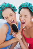Friends in hair rollers holding hairbrush