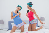 Girls in hair rollers singing with hairbrush