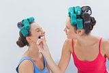 Friends in hair rollers having fun with makeup