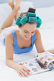 Smiling girl in hair rollers lying on bed