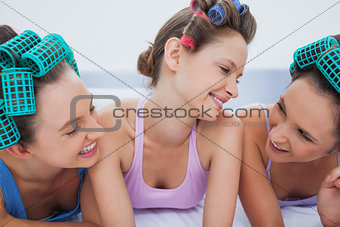 Girls in hair rollers relaxing in bed and talking