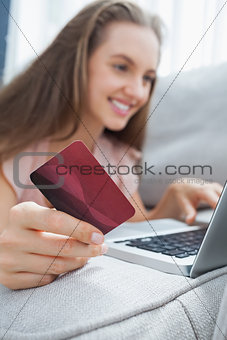 Smiling woman lying ona sofa holding a card and laptop