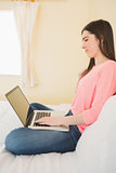 Smiling girl using a laptop sitting on her bed
