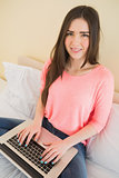 Cheerful girl looking at camera using a laptop sitting on a bed