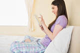 Smiling girl sitting on a bed looking and using a tablet pc