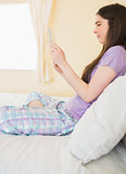 Happy girl sitting on a bed looking and using a tablet pc