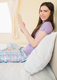 Content girl sitting on a bed looking at camera and using a tablet pc