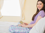 Relaxed girl sitting on a bed looking at camera and using a tablet pc