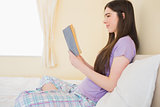 Smiling girl sitting on a bed reading a book
