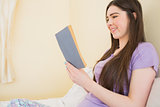 Happy girl sitting on a bed reading a book