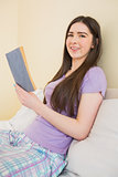 Cheerful girl looking at camera and sitting on a bed reading a book