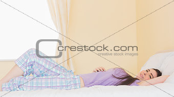 Cheerful girl lying on a bed and looking at camera