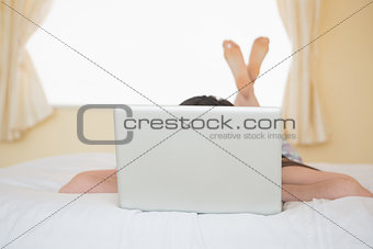 Girl lying on a bed hiding behind a laptop