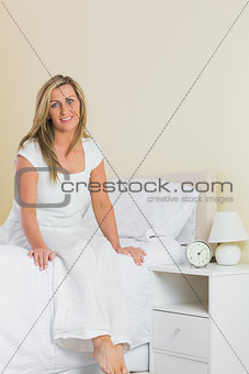 Pleased woman looking at camera and sitting on a bed
